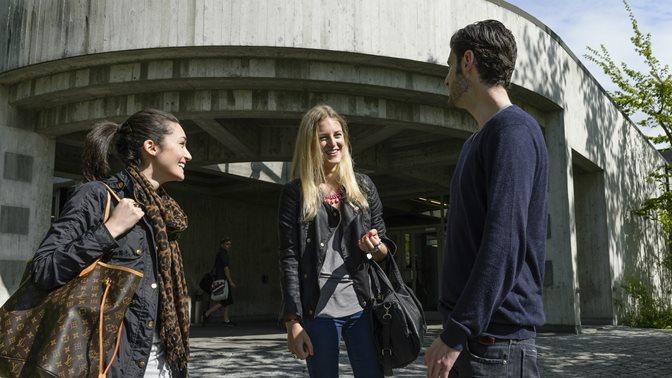 Studierende vor dem Eingang des Bibliotheksgebaeudes an der Universitaet St.Gallen (HSG)