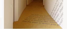Flur im HSG Alumni Haus mit einem bodenübergreifenden Schriftzug als Wanddekoration.